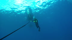 Diver swimming with rope near boat in ocean - stock footage