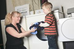 A kid with mother on the dryer having fun - stock photo