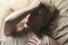 A woman feel sick lying down on bed Stock Photos