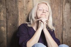 A senior person pray with a wood background Stock Photos