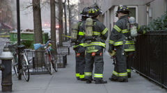 FDNY firefighters huddled NYC street smoke firetrucks background Manhattan NY 4K Stock Footage