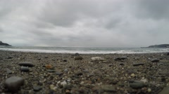 4K Cloudy skies over pebbly beach, tide coming in, closeup of sand and stones Stock Footage