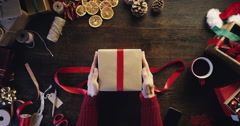 Top view hands wrapping christmas presents at wooden desk from above - Red Epic Stock Footage