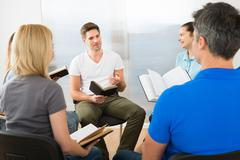 Man Explaining To His Friends From Scripture Stock Photos