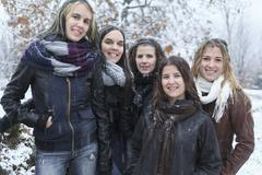 A Group of excited young girl friends outdoors in winter - stock photo