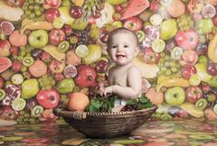 Happy little baby girl with fruits on the basket - stock photo