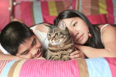 Asian kid lay on his bedroom with cat Stock Photos