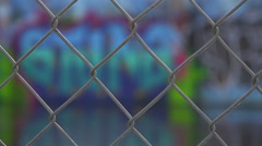 Focus through a chain link fence to reveal urban graffiti. - stock footage
