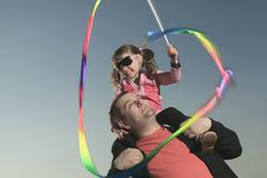A Little girl play with is dad on sunset - stock photo