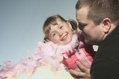 A funny Little girl play with is dad on sunset - stock photo