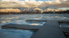 Timelapse of Provo Boat Harbor frozen as clouds move over the mountains. Stock Footage