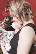 Stock Photo of A christmas toddler with is mother in front of a fir