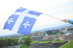 A Quebec flag on the hand of a man - stock photo