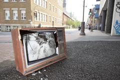 An old broken TV left on the street - stock photo