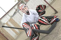 A young teen hockey goaler outside in the arena Stock Photos