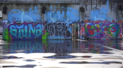 Colorful graffiti adorns an abandoned building in an urban area. - stock footage