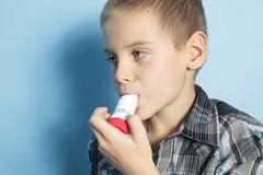 Asthma boy with is inhalator over blue background Stock Photos