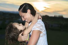 Beautiful mother and daughter in sunset sun beams Stock Photos