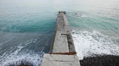 Old ruined pier on pebbly beach. Winter Stock Footage