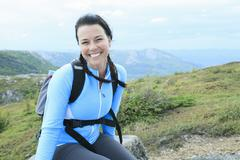 Female hiker with backpack walking and smiling on a country trai Stock Photos