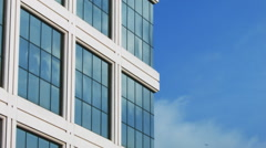 OFFICE BUILDING CORNER AGAINST A CLEAR BLUE SKY EXTERIOR / DAY Stock Footage