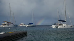 Rainbow in the distance sailboats at anchor, Cooper Island BVI Stock Footage