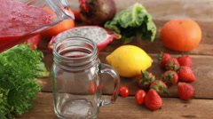 Pouring a healthy, red smoothie made of blended fruits and vegetables. Stock Footage