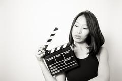 Young beautiful asian woman looking at  clapperboard black and white Stock Photos