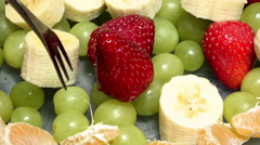 Tip pierces green grapes in a bowl of fruit on a fork stringing Stock Footage