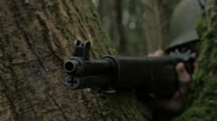 WW2 American infantry  soldier aims Grand rifle behinde tree Stock Footage