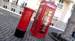 Skew angle of an Iconic Red Post Box and Red  Phone Box in London United kingdom Stock Footage