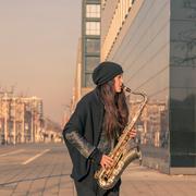 Beautiful young woman playing tenor saxophone - stock photo
