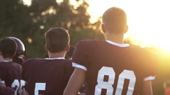 Football Players Stand on Sidelines Stock Footage
