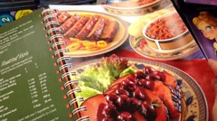 Closeup woman hand going to flip page of recipe book Stock Footage