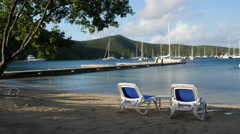 2 lounge chairs on the beach of Norman Island BVI Stock Footage