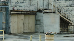 ESTABLISHING SHOT OF A DILAPIDATED WOODEN COMMERCIAL BUILDING Stock Footage