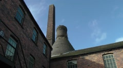 Pottery factory old bottle kiln chimney blue sky moving clouds Stock Footage