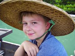 boy wearing a hat out of palmtrees for sun protection in asia - stock photo