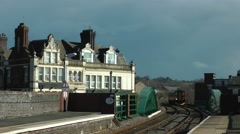 Victorian railway hotel stormy sky train approaching colourful Stock Footage