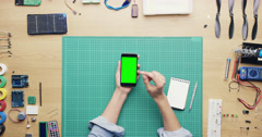 Top view woman software engineer using smartphone touchscreen at desk from above Stock Footage