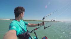 Kiter kiteboarding in sunny flat lagoon - stock footage