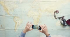 Top view woman traveler photographing locations on vintage world map desk from Stock Footage
