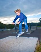 Boy jumping with scooter over the ramp Stock Photos