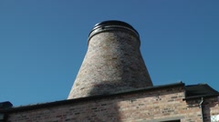Industrial architecture victorian conical pottery bottle  kiln deep blue sky Stock Footage