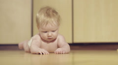 Cute little baby lying and exploring surface of floor Stock Footage