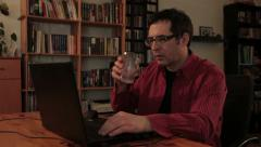 Male typing on laptop computer, take a glass of water from the table and drink. Stock Footage