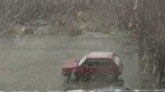 Snow storm starting over small car on parking Stock Footage