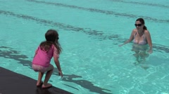 Girl child jumps into swimming pool Stock Footage