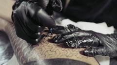 Close up shot of tattoo gun drawing on person's skin Stock Footage