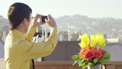 Multi-Ethnic Man On A Roof, Turns To Take A Photo Of The City View Behind Him Stock Footage